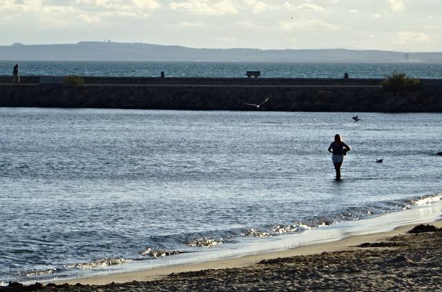 femme marchant au bord de la mer